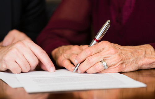 Erbrecht, Anwaltsbüro Berlin, eine Frau unterschreibt ein Dokument